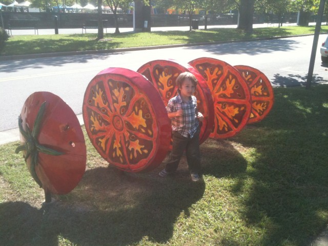My nephew standing by a sliced tomato sculpture outside the Farmer's Market in Nashville. I don't know who made it, but it appears to be plasma cut and painted steel.