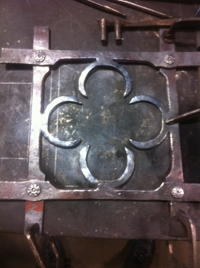 A quatrefoil design made from four flat bars riveted together, with the design hot chiseled out. No welding or grinding was used in construction.