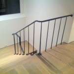 A very simplified railing - one flat bar for the top rail, a single tapered round picket on every step.